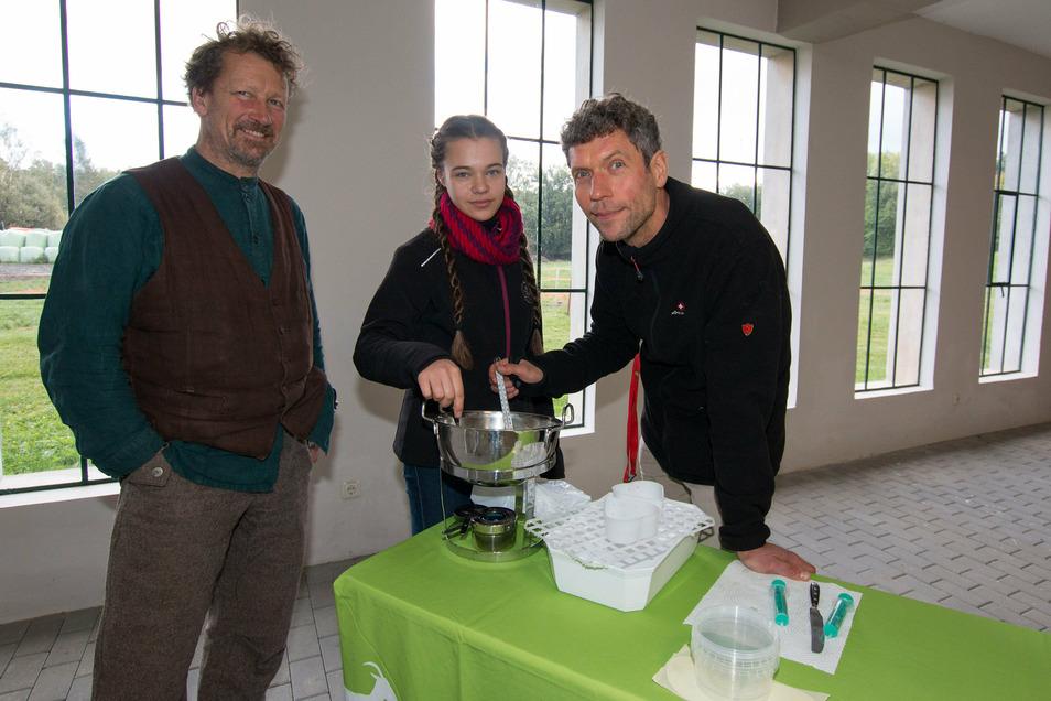 Peer Salden leitet Judith und ihren Vater Carsten Exner an, wie Käse hergestellt wird.