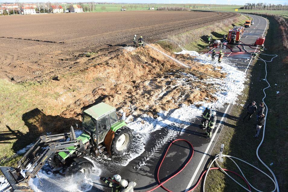Strohballen auf einem Traktor-Anhänger fing während der Fahrt Feuer. Feuerwehrkameraden und ein anderer Traktor mussten das Material abkühlen.