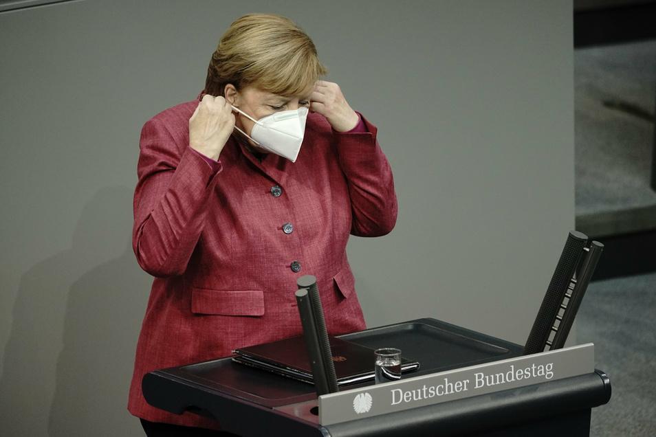 Bundeskanzlerin Angela Merkel (CDU) nimmt vor der Regierungserklärung zur Bewältigung der Corona-Pandemie die Maske ab.