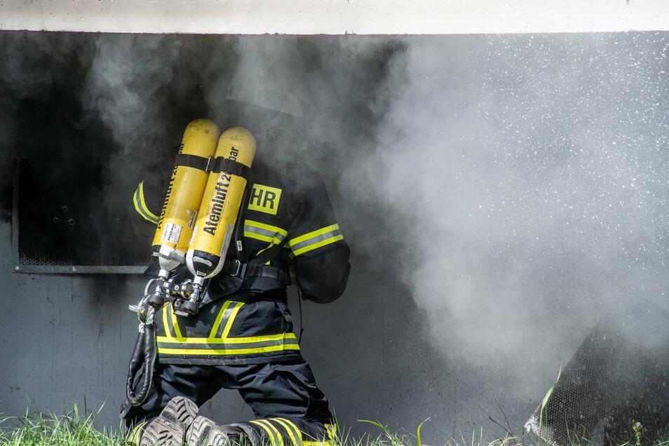 Ein Feuerwehrmann hebelt die Abdeckung eines Kellerfensters auf.