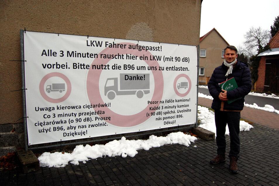 Mike Braun vom Burger Ortschaftsrat vor einem der Ende 2019 im Dorf platzierten Plakate, die Lkw-Fahrer bitten, den Ort möglichst zu meiden.