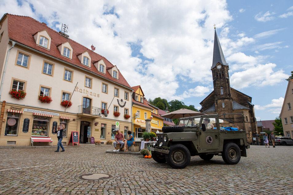 """Am Set von """"Der Ranger - Paradies Heimat"""" 2019 in Stadt Wehlen. Philipp Danne sitzt im Jeep, auf der Bank am Brunnen sitzen seine Schauspiel-Kollegen Sebastian Kaufmane und Liza Tzschirner."""