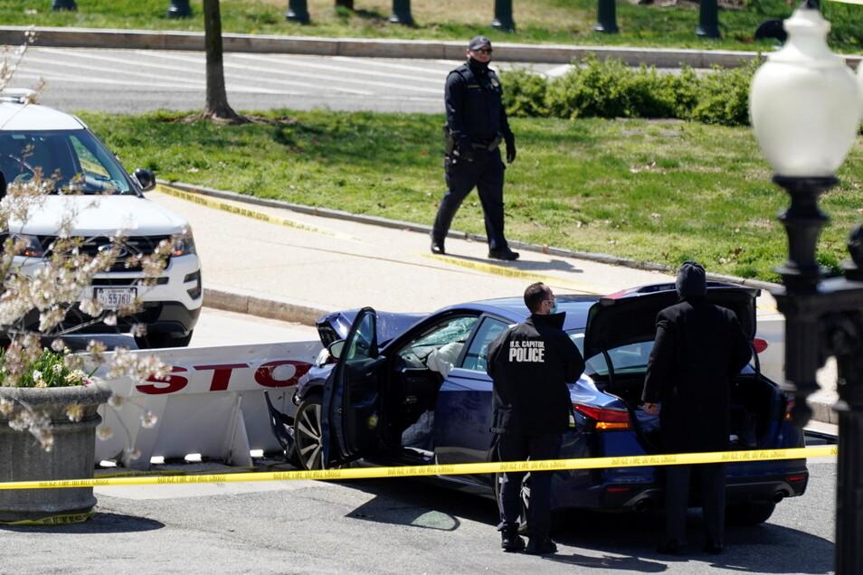 Beamte der Kapitol-Polizei stehen in der Nähe eines Autos bei einer Polizeisperre. Ein Mann hatte mit einem Auto eine Absperrung gerammt und dabei einen Polizisten getötet.