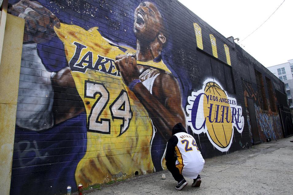 Ein Fan trauert vor einem Wandbild in Los Angeles, das den Basketballspieler Kobe Bryant darstellt. Bryant ist am Sonntag bei einem Hubschrauberabsturz in Kalifornien tödlich verunglückt.