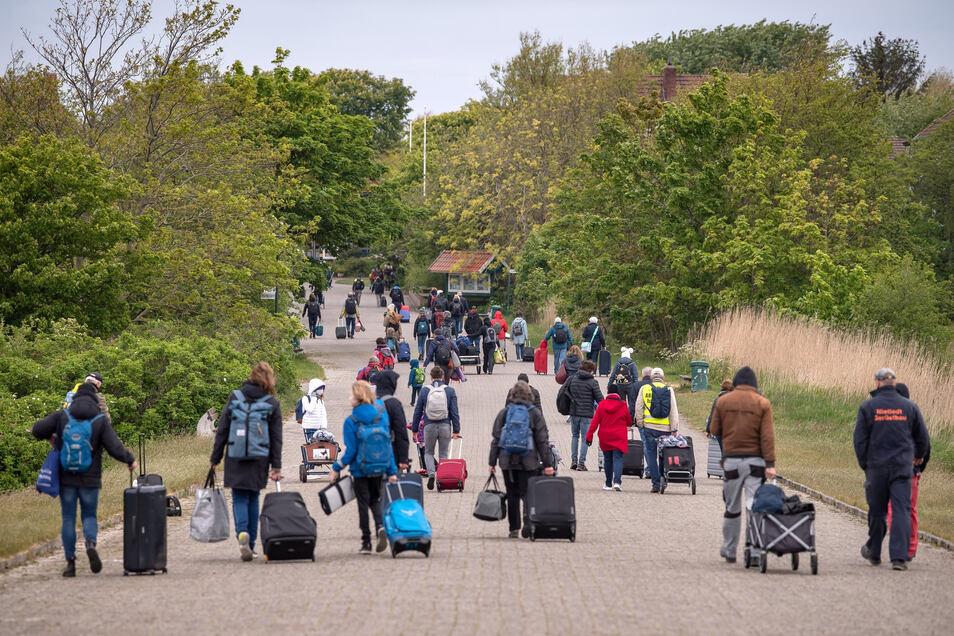 Touristen mit Koffern laufen über die Insel Spiekeroog: Zahlreiche Menschen haben die Tourismus-Lockerungen diese Woche genutzt und sind zum Urlaub auf die Ostfriesischen Inseln gefahren.
