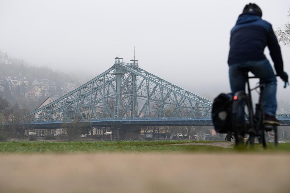 Ein Radfahrer fährt am Morgen im Nebel vor der Brücke Blaues Wunder auf den Elbwiesen in Dresden entlang.