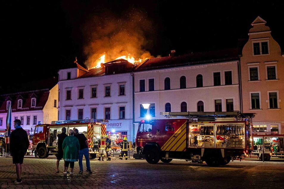 Der Dachstuhl eines Mehrfamilienhauses am Radeburger Markt stand am Freitabend in Flammen. Feuerwehrkräfte rückten zum Löscheinsatz an.