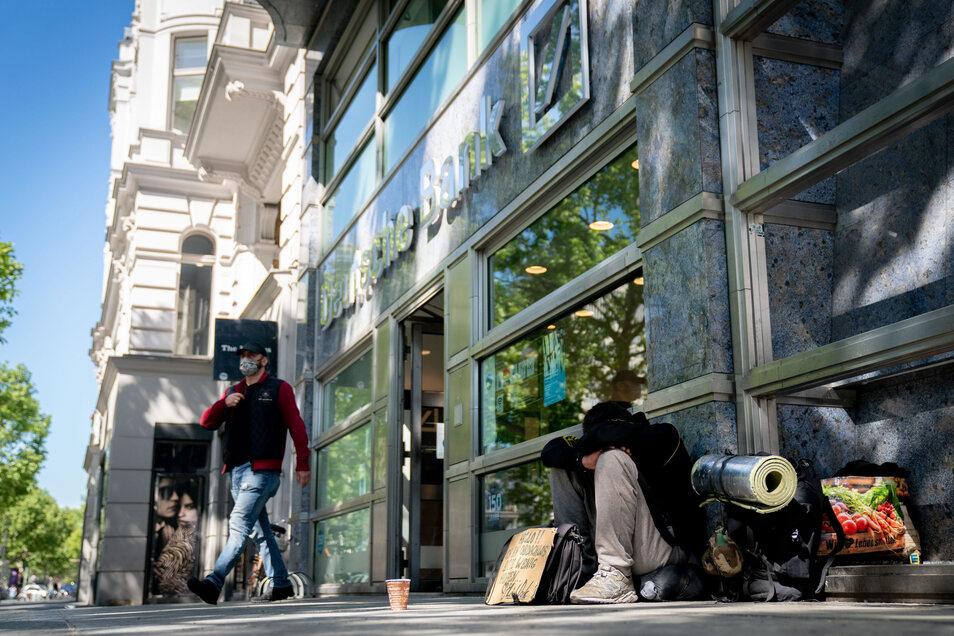 Ein Obdachloser bittet vor einer Filiale der Deutschen Bank in Berlin um Unterstützung.