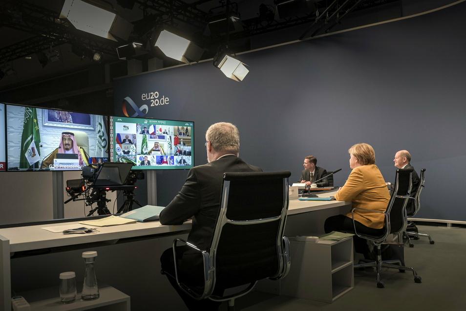 Angela Merkel, Bundeskanzlerin, und Olaf Scholz, Finanzminister, nehmen beim virtuellen G20-Gipfel an einer Videokonferenz im Kanzleramt teil, während auf den Bildschirmen Königs Salman, Gastgeber der Konferenz und König von Saudi-Arabien, zu sehen ist