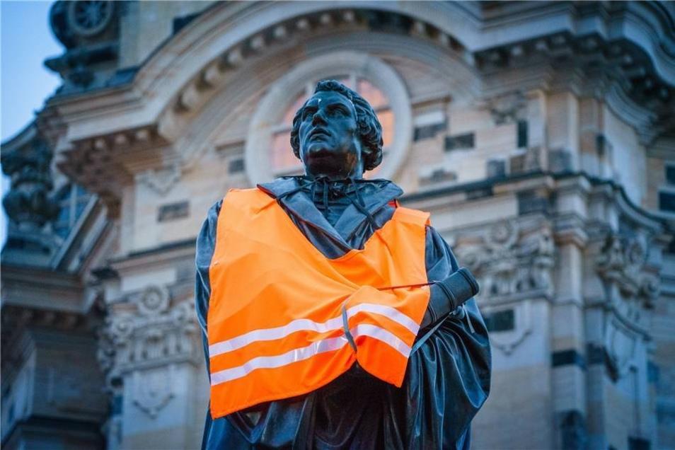 Das Lutherdenkmal vor der Frauenkirche trägt am frühen Montagabend eine Warnweste - diese ist inzwischen zum Symbol für die Dresdner Anti-Pegida-Bewegung geworden.