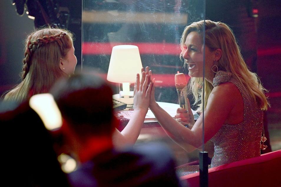 Sängerin Helene Fischer (r) spricht mit Sontje durch eine Plexiglasscheibe.