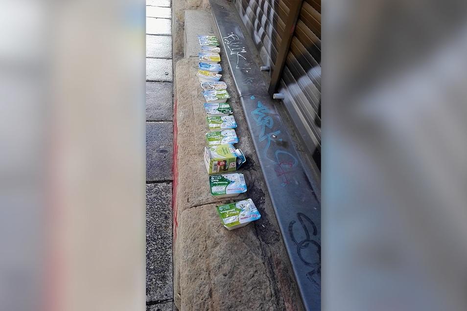 Eine Reihe von Quark-Packungen liegt auf dem Hausvorsprung. Ein Anwohner hat sie aus der Mülltonne eines Dresdner Lebensmittelmarktes gezogen. Alles sollte weggeschmissen werden. Dabei ist die Ware noch essbar.