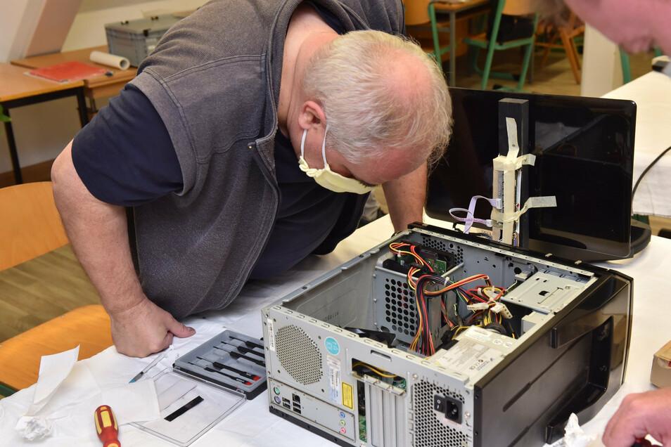 Der gelernte Elektriker Michael Eichner vom Repair-Café hilft bei der Säuberung eines Computers.