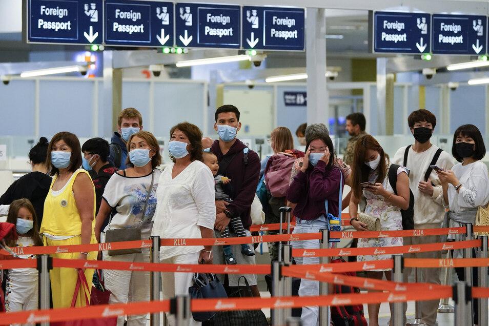 Passagiere mit Mundschutz warten an einem Flughafen auf die Einreise.