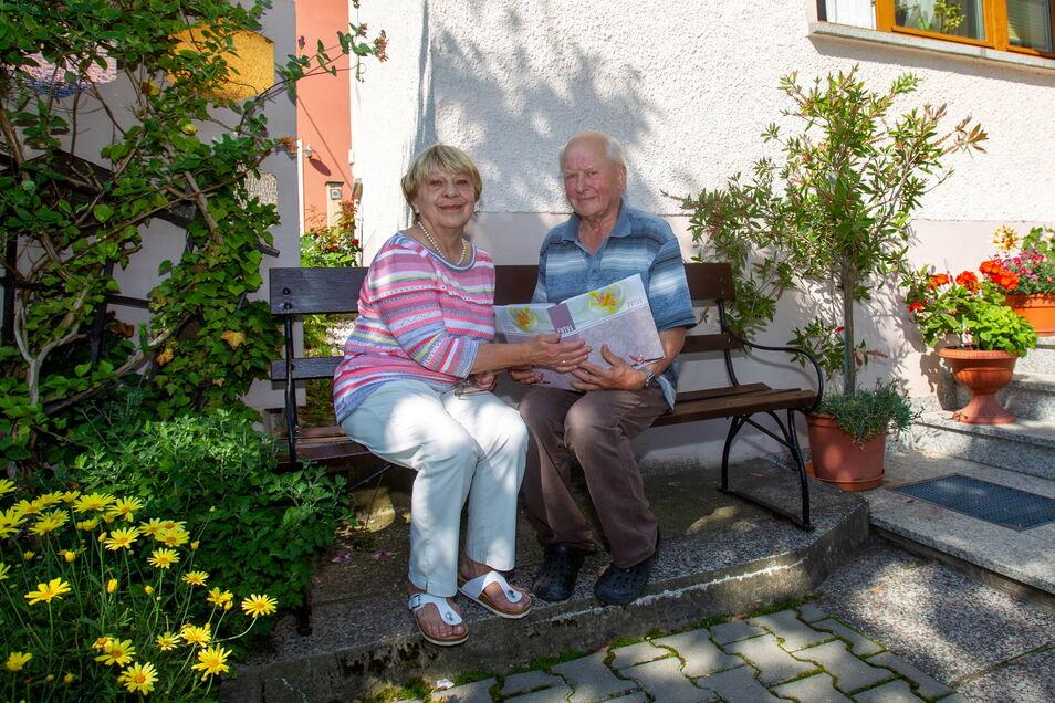 Monika und Frieder Rudolph mit einem Fotoalbum in der Hand. Beide haben 1968 eine Reise nach Ungarn unternommen und mussten wegen des Prager Frühlings eine lange Rückfahrt nach Hause mit dem Zug erdulden.