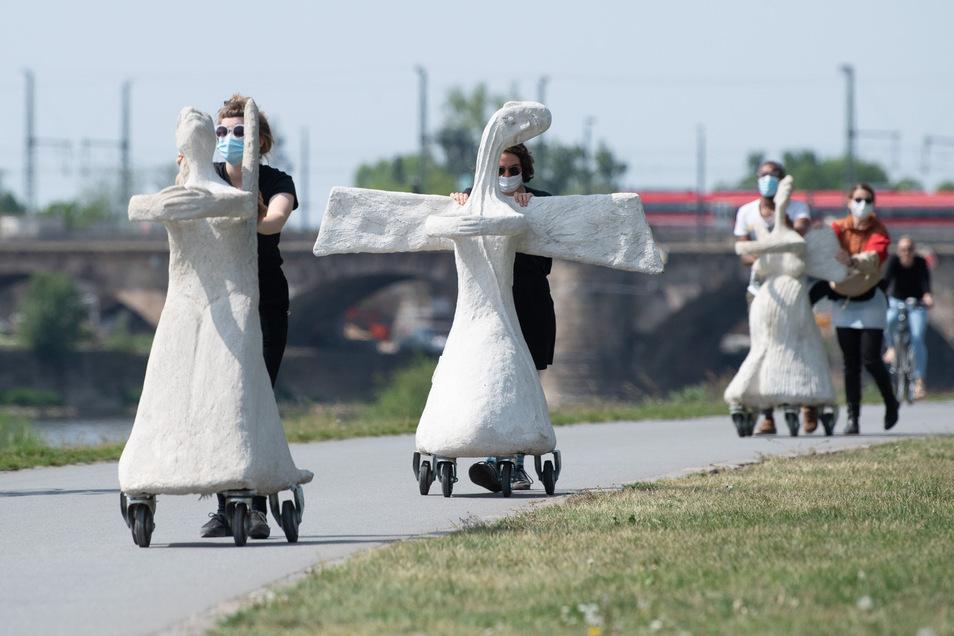"""Teilnehmerin der künstlerischen Performance unter dem Titel """"Rolling Angels"""" schieben aus Beton gefertigte Engelsskulpturen der norwegisch-dänischen Künstlerin Marit Benthe Norheim am Elbufer entlang."""