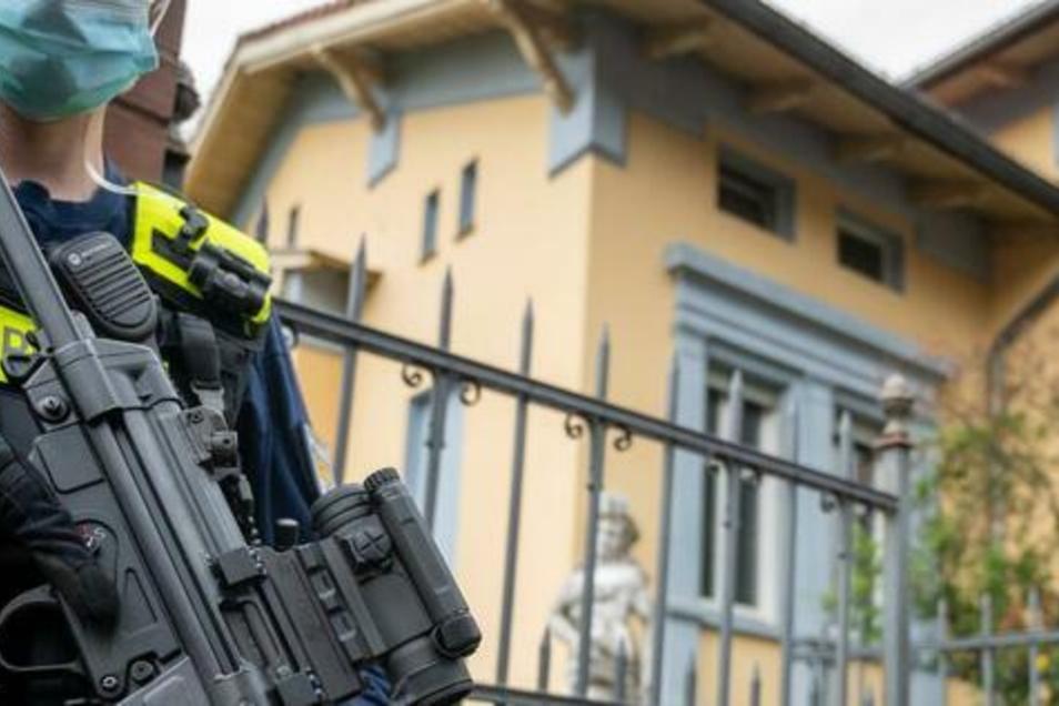 Schwer bewaffnete Polizisten stehen vor der Remmo-Villa im Berliner Stadtteil Alt-Buckow.