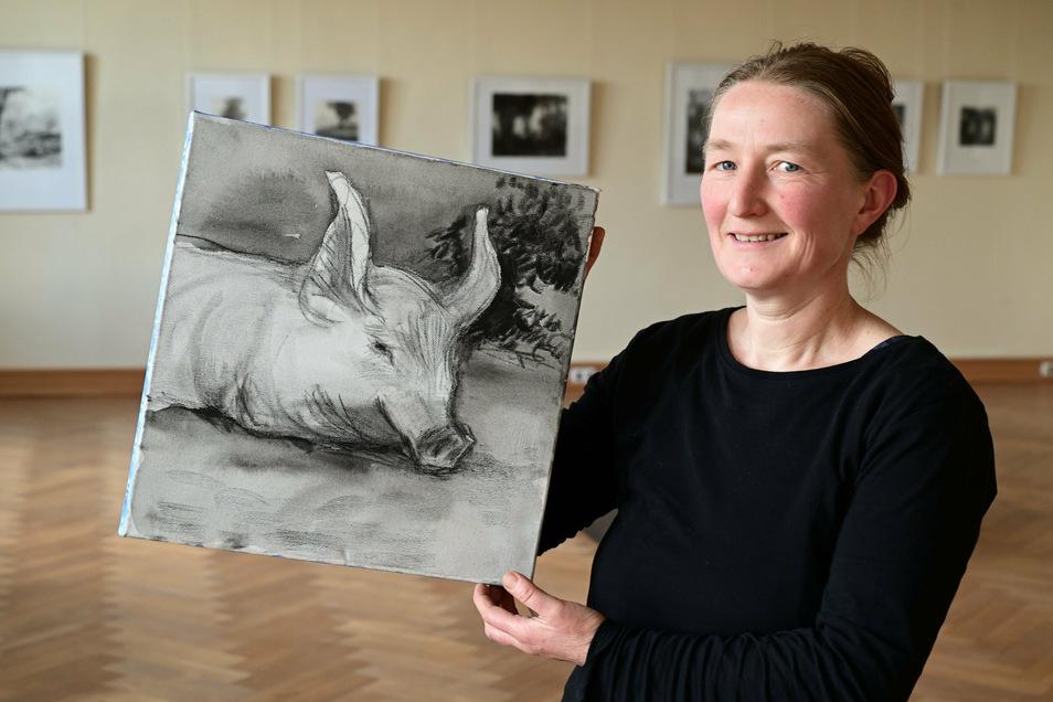 """Elisabeth Richter in ihrer Ausstellung im Schloss Struppen mit der Zeichnung """"Ferkel"""", Graphit auf Leinwand, 2019."""