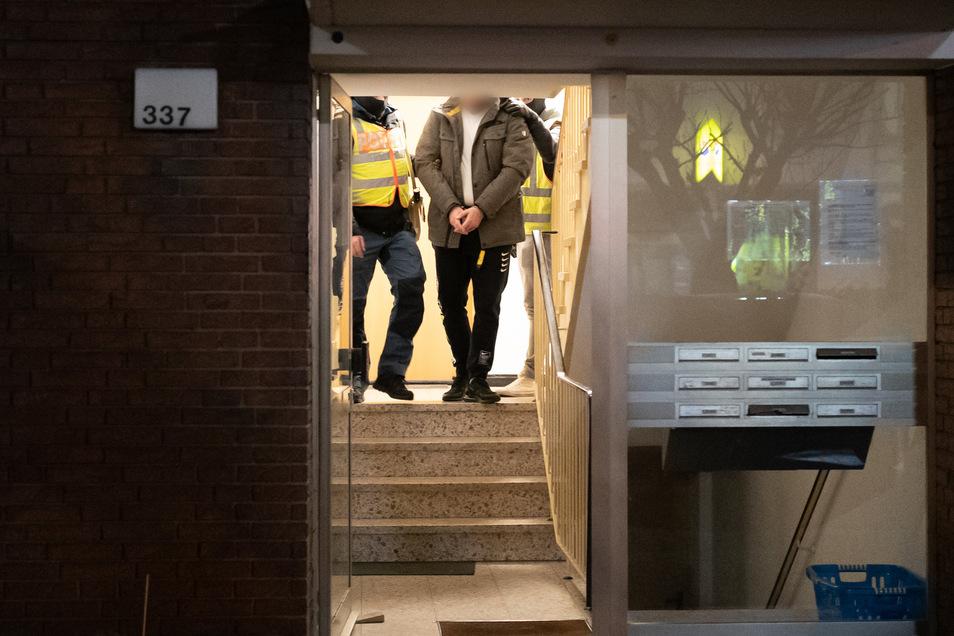 Beamte der Polizei führen einen vorläufig festgenommenen Mann aus einem Mehrfamilienhaus in Datteln.