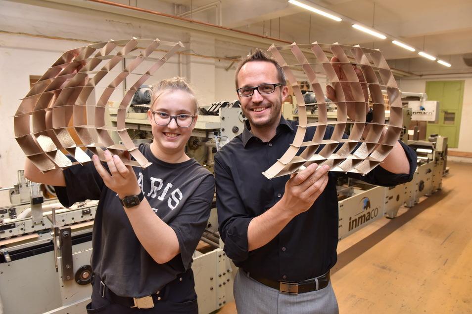 Wer schafft es wie schnell, diese Gebilde zusammenzustecken? Ronny Ruider und Azubi Lauren Wöller von der Glashütter Pappen- und Kartonagenfabrik laden am Sonnabend in Pirna dazu ein, es zu probieren.