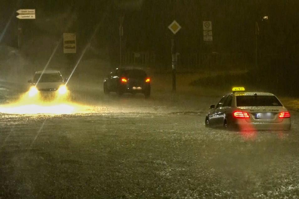 Ein Taxi, das sich im Hochwasser festgefahren hat, steht auf einer überschwemmten Straße. Starkregen setzte am Donnerstagabend einige Straßen in Essen unter Wasser.