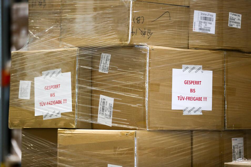 """Schilder """"Gesperrt bis TÜV-Freigabe"""" kleben auf Kartons mit unzertifizierten Schutzmasken aus China."""