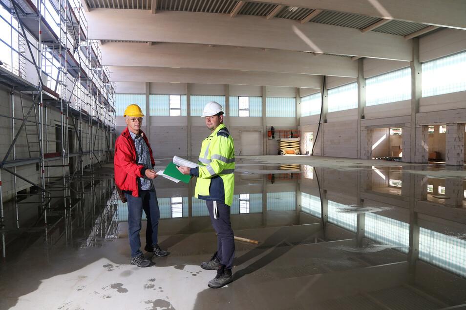 Steffen Uschner (l.) vom Riesaer Stadtbauamt und Bauüberwacher Denny Wolf führen über die Oberschulbaustelle an der Merzdorfer Straße - hier in der neuen Turnhalle.