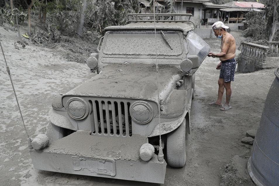 Ein Bewohner kontrolliert seinen mit Vulkanasche bedeckten Jeep vor seinem Haus in Laurel in der Provinz Batangas.