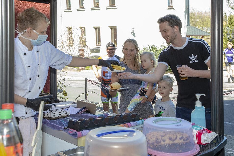 Nadine, Hannah, Niklas und Thomas aus Freital freuen sich am Ostersonntag auf Pommes und Wurst beim Straßenverkauf am Hotel zur Linde in Freital.