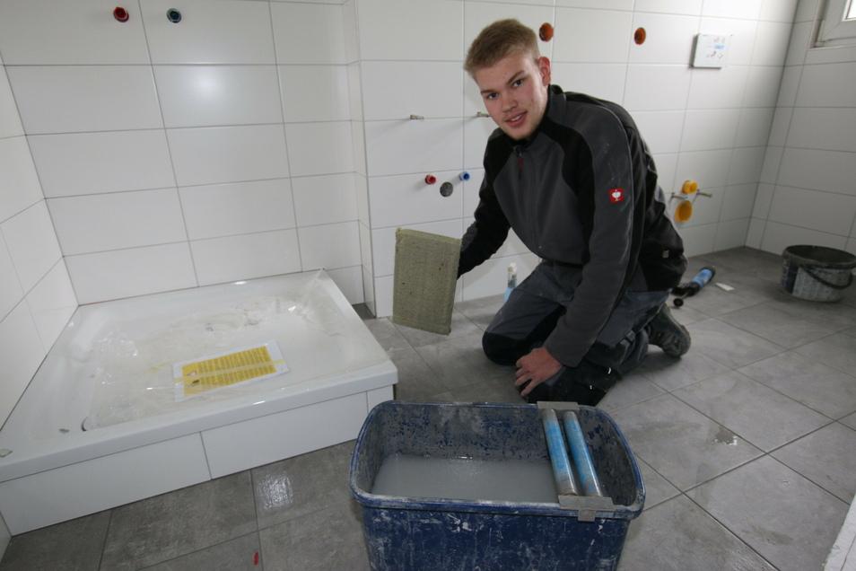Willy Künstler, Lehrling im ersten Lehrjahr, unterstützt die Fliesenlegearbeiten im Reinsdorfer Dorfgemeinschaftshaus.