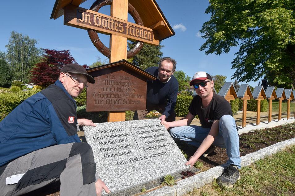 Die Steinmetze Christian, Helmut und Axel Müller (von links) stellten die Gedenktafel auf dem Lawalder Friedhof auf.