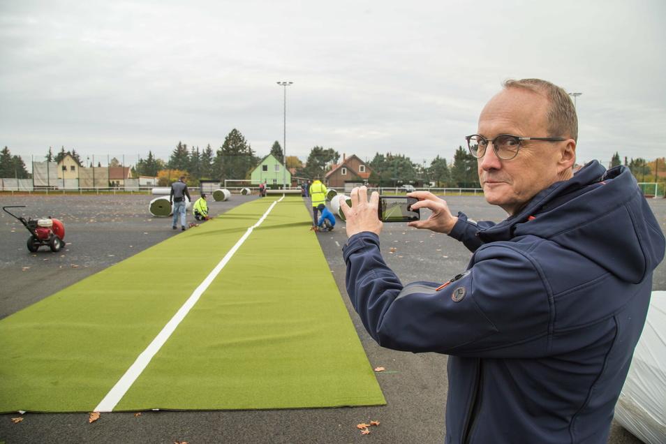 Endlich: Nieskys Jahnsportplatz hat einen neuen Kunstrasen. Ingenieur Stephan Lehmann vom Ingenieurbüro Lehmann macht schnell ein Foto vom Ausrollen.