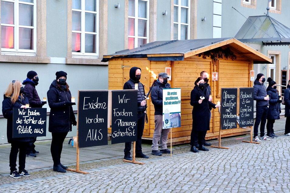 In schwarzer Trauerkleidung und mit Plakaten, Kerzen und Fackeln haben sich die Mitarbeiter des Hotels- und Restaurants Goldener Anker vor das Haus gestellt.