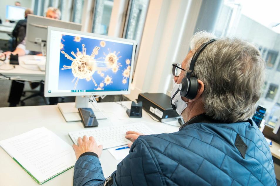 Ein Mitarbeiter sitzt in der Zentralen Unterstützung der Kontaktnachverfolgung vor einem Computer, auf dessen Bildschirm der Hamburger Pandemie-Manager angezeigt wird.