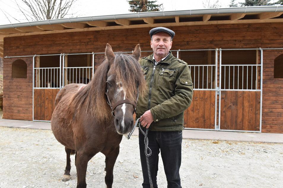 Siegfried Horn mit Ponystute Wolke vor dem nach einem Brand durch Spenden wieder aufgebauten Stall.