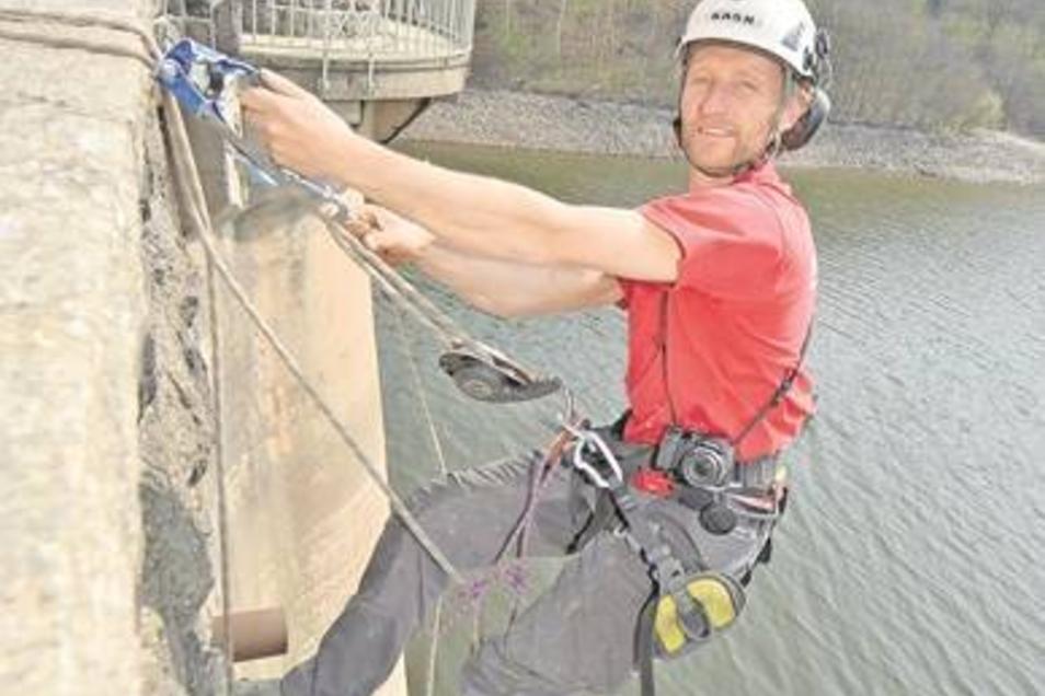 Torsten Süßmilch ist Spezialkletterer bei der Seiltechnik Dresden. Er seilt sich ab, um Probebohrungen an der Staumauer zu nehmen. Damit er arbeiten kann, wurde der Wasserspiegel abgesenkt. Weite Teile des Sees, vor allem an den flachen Stellen, liegen de