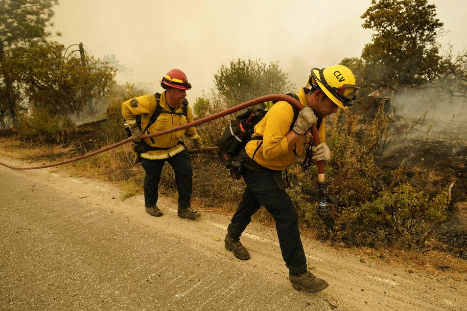 USA, Tollhouse: Feuerwehrleute gehen eine Straße entlang, nachdem das Creek Fire in der Gegend wütete.