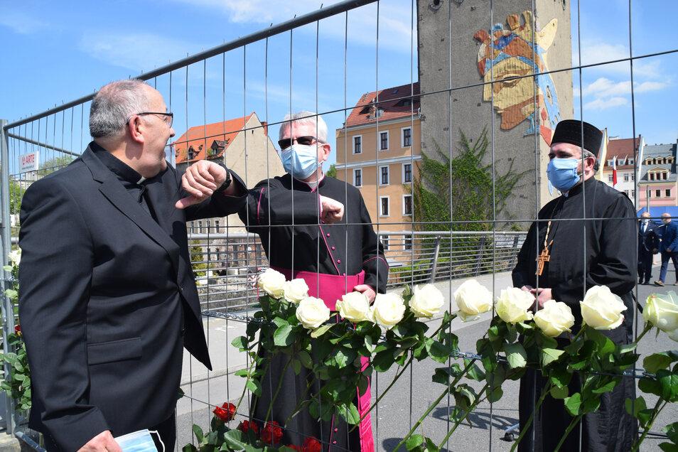 Begrüßung in Corona-Zeiten auf der Görlitzer Altstadtbrücke: Der Görlitzer katholische Bischof Wolfgang Ipolt mit Armgruß durch den Absperrzaun mit dem Dekan von Zgorzelec Jan Kulyna.