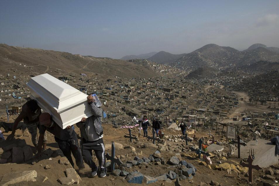 Verwandte tragen den Sarg ihres Angehörigen während einer Beerdigung in dem für COVID-19-Fälle reservierten Teil des Friedhofs von Nueva Esperanza in Lima, Peru.