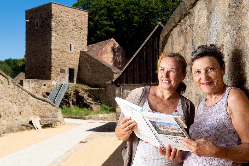 Schlosschefin Katja Altmann (l.) und Birgit Frech vom Schlossverein stehen an der Befestigungsmauer von Schloss Klippenstein in Radeberg. Im Hintergrund ist der Eulenturm zu sehen. Beide Frauen haben sich sehr für den Wiederaufbau des Schlosses und des Tu