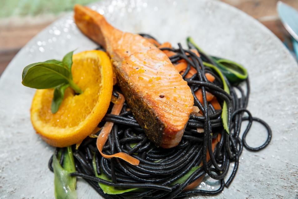 Fisch mit fetziger Optik: Dieses gebratene Lachsfilet schwimmt auf Wellen aus schwarzen Spaghetti.
