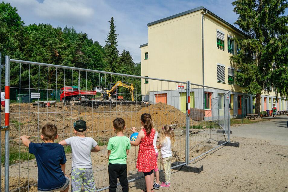 Die Kinder der Hummelburg in Großpostwitz haben jetzt zwar weniger Fläche zum Spielen, dafür aber viel zu schauen. Mit schwerem Gerät beginnen derzeit die Arbeiten für einen neuen Anbau.