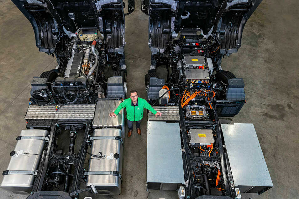 Vom Verbrenner (l.) zum Stromer (r.): Framo-Mitarbeiter Michael Klopfer zwischen zwei Lkw. Der Dieselmotor der links geparkten MAN-Zugmaschine wird noch durch ein Elektroaggregat getauscht. Damit hat Framo prominenten Konkurrenten etwas voraus.