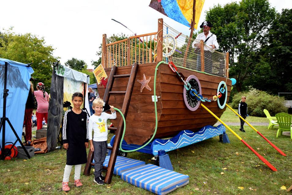 """Madya und Elias haben Spaß am Piratenschiff. Auf dem Schiff steht Thomas der Schreckliche (Thomas Stolle). Vor den """"Bühnenvorhängen"""" links tritt derweil das Duo """"Leichtfuß und Liederliesel"""" auf; Letztere ist hier mal von hinten zu sehen."""