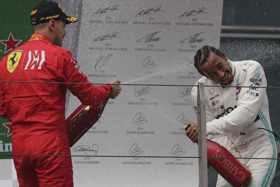 Lewis Hamilton wird von Sebastian Vettel (l) während der Preisverleihung mit Champagner besprüht.