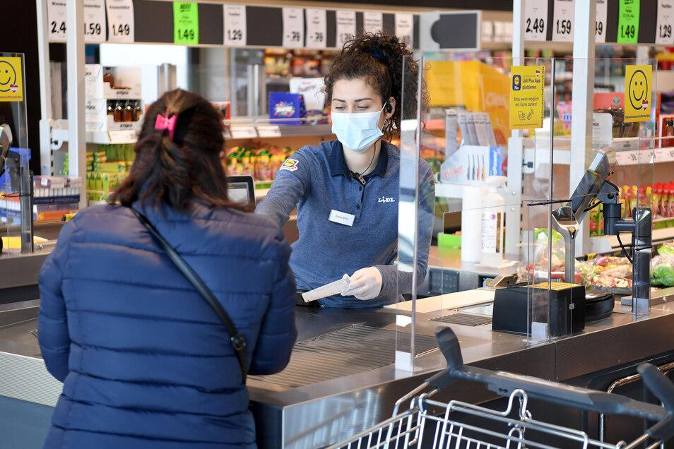 Supermärkte haben Plexiglas als Spuckschutz installiert, um Tröpfchen von Kunden abzufangen.