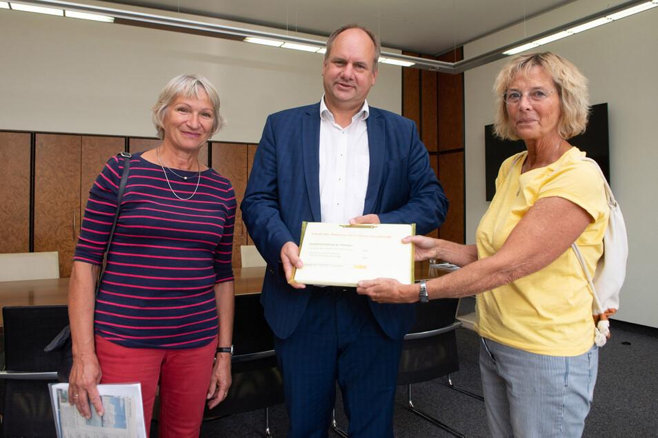 Ingrid Hoffmann (l.) und Beate Handschack haben Oberbürgermeister Dirk Hilbert (FDP) zur Bürgersprechstunde im Rathaus ihre Unterschriftenliste übergeben. Mehr als 9.000 Unterstützer haben sie für ihre geforderte Rettung des Stausees gewonnen.