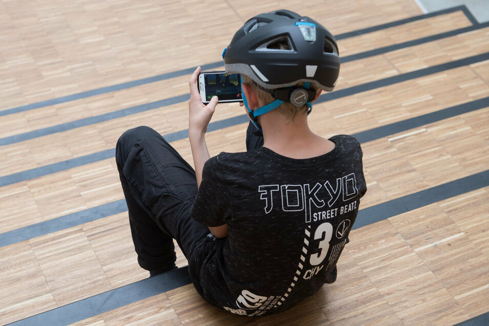 Zocken in der Pause: Ein Schüler sitzt auf einer Freitreppe und spielt auf seinem Smartphone.