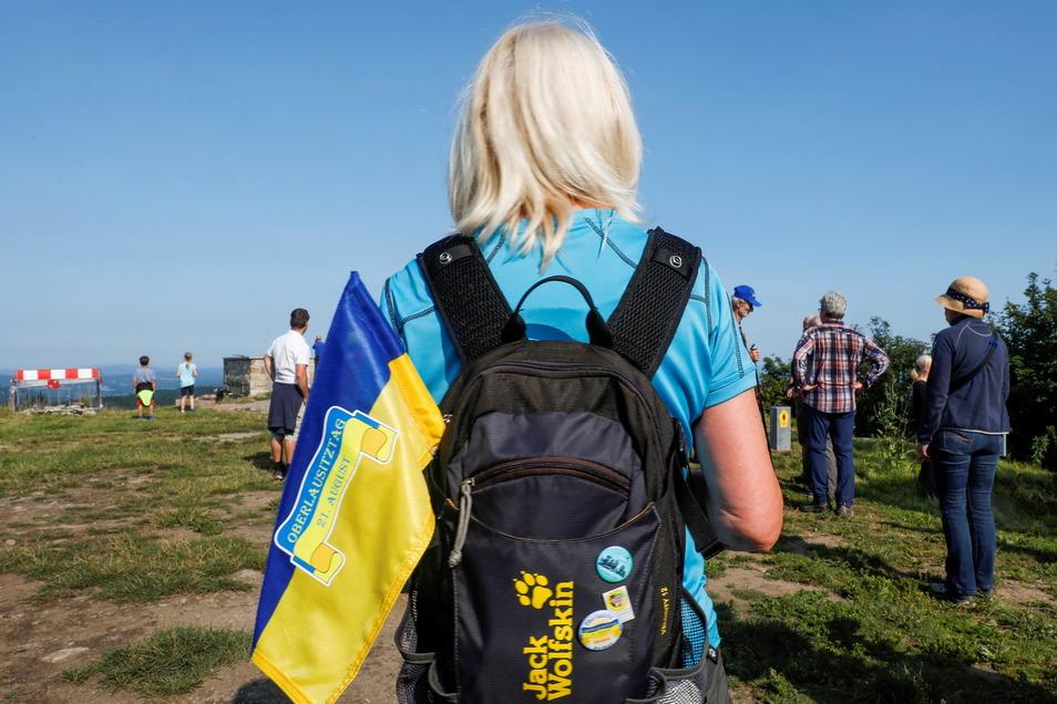 Heimatliebe im Rucksack: Diese Besucherin beim kleinen Festakt auf der Lausche trägt die blau-gelbe Fahne der Oberlausitz.