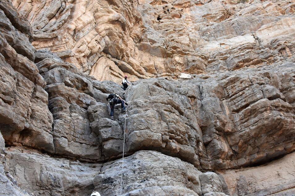 Auf Abstand: Die Via Ferrata führt auf schmalem Grat an einem Fels des Hajar-Gebirges entlang.